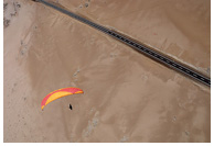 Paraglider aproaching a landing zone near the Rio Seco point, San Marcos, Iquique, Atacama Desert, Chile
